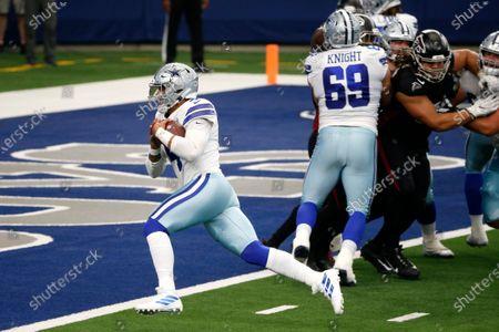 Dallas Cowboys quarterback Dak Prescott (4) reaches the end zone for a touchdown as Brandon Knight (69) provides coverage against the Atlanta Falcons in the second half of an NFL football game in Arlington, Texas