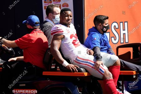 New York Giants running back Saquon Barkley (26) is carted to the locker room after being injured during the first half of an NFL football game against the Chicago Bears in Chicago