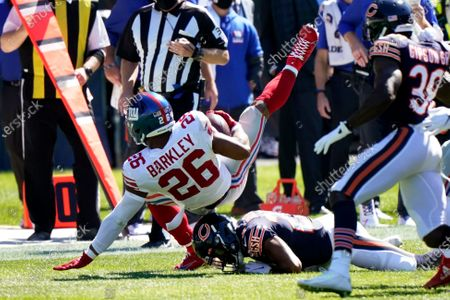 New York Giants running back Saquon Barkley (26) is brought down against the Chicago Bears during the first half of an NFL football game in Chicago