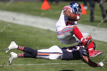 New York Giants running back Saquon Barkley (26) is brought down by Chicago Bears cornerback Kyle Fuller (23) during the first half of an NFL football game, in Chicago