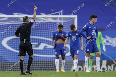 Referee Paul Tierney shows a red card to Chelsea's Andreas Christensen, not pictured, during the English Premier League soccer match between Chelsea and Liverpool at Stamford Bridge Stadium