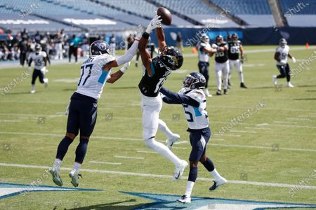 Jacksonville Jaguars wide receiver Collin Johnson (19) reaches for a pass between Tennessee Titans defenders Tennessee Titans safety Amani Hooker (37) and defensive back Chris Jackson (35) in the first half of an NFL football game, in Nashville, Tenn. The pass was incomplete
