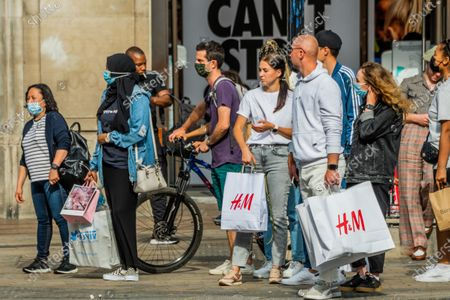 Shoppers take advantage of unseasonal weather to visit stores in pre covid numbers on Oxford Street. Just as the next stage of the tightened regulations for Coronavirusbegins to come in to force.