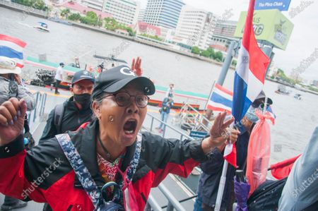 A protester shouts at the pier after arriving at the demonstration area at the Sanam Luang. Pro-democracy protesters converged at the historic royal heart of Bangkok to demand the resignation of the military-backed government and reforms of the monarchy, long considered a taboo subject in Thailand. The demonstrators gathered first at the Thammasat university campus on a college football field that was the scene of a massacre of left-wing students by pro-regime paramilitaries in 1976.