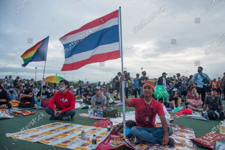 Stock Image of Protesters who stayed overnight are seen holding up flags as they prepare themselves for the demonstration in the morning. Pro-democracy protesters converged at the historic royal heart of Bangkok to demand the resignation of the military-backed government and reforms of the monarchy, long considered a taboo subject in Thailand. The demonstrators gathered first at the Thammasat university campus on a college football field that was the scene of a massacre of left-wing students by pro-regime paramilitaries in 1976.