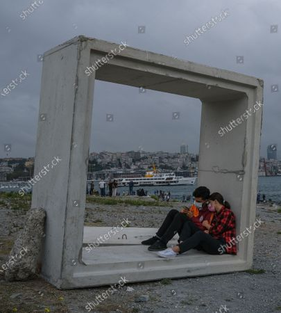 A couple sitting inside a concrete block, with the financial district Levent in the background,  next to the Bosporus on a rainy day, amid the ongoing coronavirus pandemic in Istanbul, Turkey, 20 September 2020. Turkish authorities have now allowed the reopening of restaurants, cafes, parks and beaches, as well as lifting the ban on inter-city travel, as the country eases the restrictions it had imposed in a bid to stem the spread of the ongoing pandemic of the COVID-19 disease caused by the SARS-CoV-2 coronavirus.