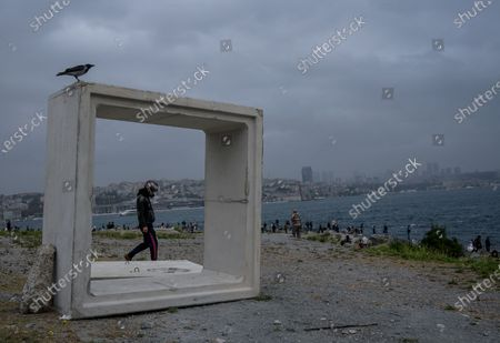 A motorcyclist walks near the concrete block with the financial district Levent in the background next to the Bosporus on a rainy day, amid the ongoing coronavirus pandemic  in Istanbul, Turkey, 20 September 2020. Turkish authorities have now allowed the reopening of restaurants, cafes, parks and beaches, as well as lifting the ban on inter-city travel, as the country eases the restrictions it had imposed in a bid to stem the spread of the ongoing pandemic of the COVID-19 disease caused by the SARS-CoV-2 coronavirus.