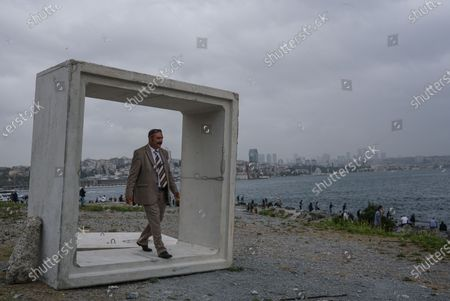A man walks inside the concrete block with the financial district Levent in the background next to the Bosporus on a rainy day, amid the ongoing coronavirus pandemic  in Istanbul, Turkey, 20 September 2020. Turkish authorities have now allowed the reopening of restaurants, cafes, parks and beaches, as well as lifting the ban on inter-city travel, as the country eases the restrictions it had imposed in a bid to stem the spread of the ongoing pandemic of the COVID-19 disease caused by the SARS-CoV-2 coronavirus.