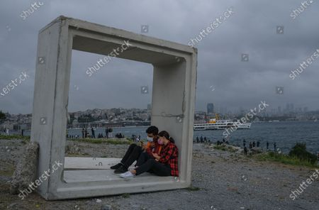 A couple sitting inside the concrete block with the financial district Levent in the background next to the Bosporus on a rainy day, amid the ongoing coronavirus pandemic  in Istanbul, Turkey, 20 September 2020. Turkish authorities have now allowed the reopening of restaurants, cafes, parks and beaches, as well as lifting the ban on inter-city travel, as the country eases the restrictions it had imposed in a bid to stem the spread of the ongoing pandemic of the COVID-19 disease caused by the SARS-CoV-2 coronavirus.