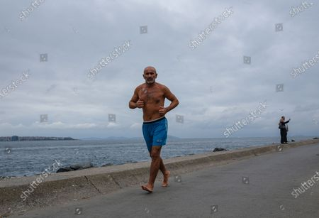 A man runs next to the Bosporus on a rainy day, amid the ongoing coronavirus pandemic  in Istanbul, Turkey, 20 September 2020. Turkish authorities have now allowed the reopening of restaurants, cafes, parks and beaches, as well as lifting the ban on inter-city travel, as the country eases the restrictions it had imposed in a bid to stem the spread of the ongoing pandemic of the COVID-19 disease caused by the SARS-CoV-2 coronavirus.