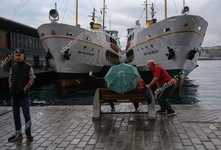 People take selfie in front of the karaoke ferry station near Bosporus on a rainy day, amid the ongoing coronavirus pandemic  in Istanbul, Turkey, 20 September 2020. Turkish authorities have now allowed the reopening of restaurants, cafes, parks and beaches, as well as lifting the ban on inter-city travel, as the country eases the restrictions it had imposed in a bid to stem the spread of the ongoing pandemic of the COVID-19 disease caused by the SARS-CoV-2 coronavirus.