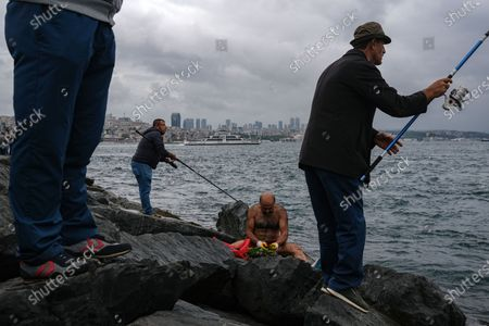 A mussel collector cleans mussel while people fish on a rainy day, amid the ongoing coronavirus pandemic  in Istanbul, Turkey, 20 September 2020. Turkish authorities have now allowed the reopening of restaurants, cafes, parks and beaches, as well as lifting the ban on inter-city travel, as the country eases the restrictions it had imposed in a bid to stem the spread of the ongoing pandemic of the COVID-19 disease caused by the SARS-CoV-2 coronavirus.
