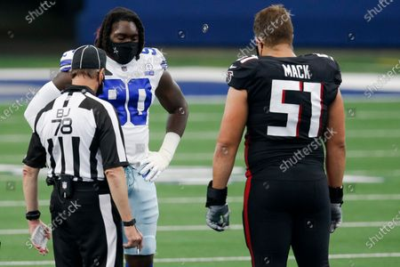 Back judge Greg Meyer (78) tosses a coin as Dallas Cowboys defensive end DeMarcus Lawrence (90) and Atlanta Falcons center Alex Mack (51) look on before an NFL football game, in Arlington, Texas. Dallas won 40-39