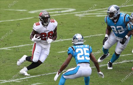 Tampa Bay Buccaneers running back Leonard Fournette (28) runs at Carolina Panthers defensive tackle Zach Kerr (92) and cornerback Troy Pride (25) during the first half of an NFL football game, in Tampa, Fla