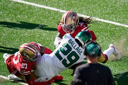 San Francisco 49ers' Dontae Johnson (27) and Marcell Harris (36) tackle New York Jets Kalen Ballage (29) during the second half of an NFL football game, in East Rutherford, N.J. The 49ers won 31-13