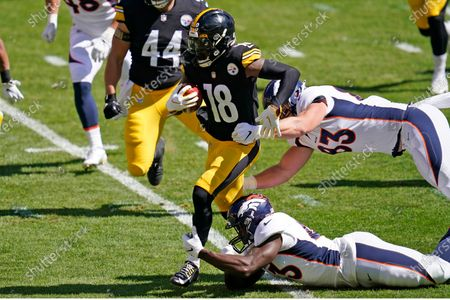 Pittsburgh Steelers wide receiver Diontae Johnson (18) breaks the tackles of Denver Broncos tight end Andrew Beck, top right, and Joe Jones, bottom right, during the first half of an NFL football game, in Pittsburgh