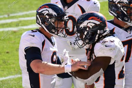 Denver Broncos quarterback Jeff Driskel (9) celebrates with Melvin Gordon (25) after the two connected on a pass play for a touchdown during the second half of an NFL football game in Pittsburgh