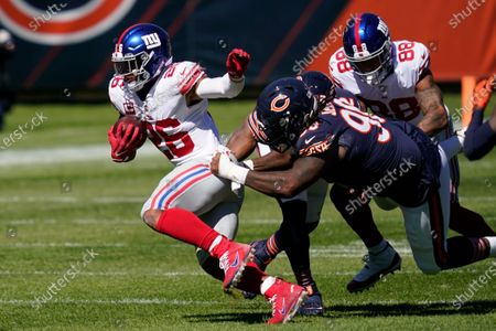 New York Giants running back Saquon Barkley (26) tries to break free from Chicago Bears defensive tackle John Jenkins (90) during the first half of an NFL football game in Chicago