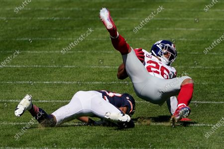 New York Giants running back Saquon Barkley (26) is brought down by Chicago Bears cornerback Kyle Fuller (23) during the first half of an NFL football game in Chicago