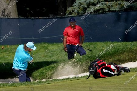 Stock Picture of Thomas Pieters, of Belgium, plays a shot from a bunker on the second hole as Patrick Reed, of the United States, looks on during the final round of the US Open Golf Championship, in Mamaroneck, N.Y