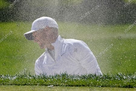 Alex Noren, of Sweden, turns his head as sand blows back in his face after playing a shot out of a bunker on the second hole during the final round of the US Open Golf Championship, in Mamaroneck, N.Y