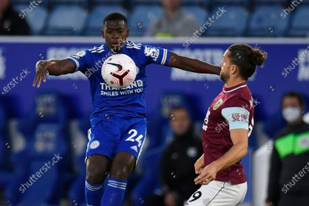 Leicester's Nampalys Mendy, left, vie for the ball with Burnley's Jay Rodriguez during the English Premier League soccer match between Leicester City and Burnley at the King Power Stadium, Leicester, England