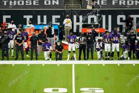 Baltimore Ravens quarterback Lamar Jackson (8) Robert Griffin III (3) head coach John Harbaugh, Anthony Levine Sr. (41) Marquise Brown (15) and other coaches and players stand and kneel during the national anthem before an NFL football game against the Houston Texans, in Houston