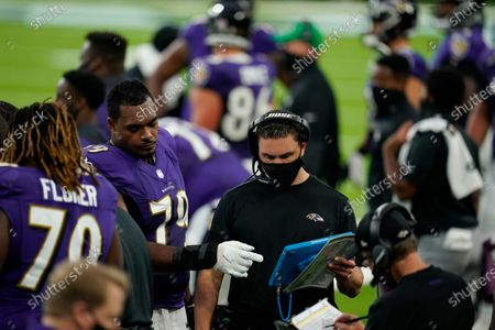 Baltimore Ravens tackle Ronnie Stanley (79) looks on an Microsoft Surface tablet with coaches on the sideline during an NFL football game against the Houston Texans, in Houston