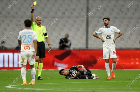 Referee Hakim Ben El Hadj shows Marseille's Yuto Nagatomo, left, a yellow card during the French League One soccer match between Marseille and Lille at the Stade Velodrome in Marseille, France