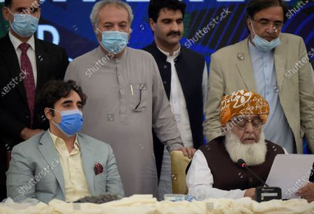 Pakistani opposition parties leaders Maulana Fazal-ur-Rehman, front right, reads out a statement while Bilawal Bhutto Zardari, front left, looks on at a press briefing following their All Parties Conference, in Islamabad, Pakistan, Sunday, Sept. 20. 2020. Pakistani opposition parties demanded immediate resignation of Prime Minister Imran Khan and they launched an alliance to hold a countrywide protest movement against the government