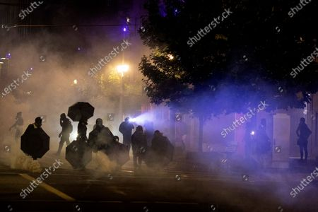 Tear gas fills the air during protests in Portland, Ore. The protests, which began over the killing of George Floyd, often result frequent clashes between protesters and law enforcement. Vandalism but no arrests occurred during a demonstration in downtown Portland involving about 200 people Saturday, Sept. 19, 2020. Frequently violent protests have racked the city for more than three months since the police killing of George Floyd in Minneapolis. Protesters want city officials to slash the police budget and reallocate money to Black residents and businesses. Some demonstrators also demand the resignation of the city's mayor