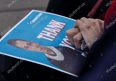 """Stock Photo of An attendee holds onto a """"thank you"""" poster during a public remembrance to honor the life and legacy of U.S. Supreme Court Justice and former Brooklynite Ruth Bader Ginsburg, outside Brooklyn's, Municipal Building, in New York. Brooklyn Borough President Eric Adams is calling on Mayor Bill de Blasio to rename the Municipal Building in honor of Justice Ginsburg, a Brooklynite who passed away Friday at the age of 87"""