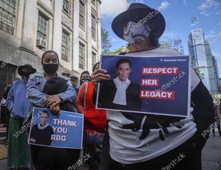 Stock Picture of People hold signs of tribute during a public remembrance to honor the life and legacy of U.S. Supreme Court Justice and former Brooklynite Ruth Bader Ginsburg, outside Brooklyn's, Municipal Building, in New York. Brooklyn Borough President Eric Adams is calling on Mayor Bill de Blasio to rename the Municipal Building in honor of Justice Ginsburg, a Brooklynite who passed away Friday at the age of 87