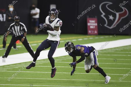 Houston Texans wide receiver Kenny Stills (12) makes a catch in front of Baltimore Ravens cornerback Anthony Averett (23) during the first half of an NFL football game, in Houston