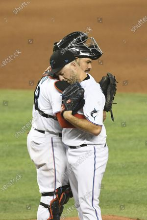 Miami Marlins catcher Jorge Alfaro and pitcher Brandon Kintzler celebrate after the team's baseball game against the Washington Nationals, in Miami