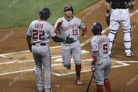 Washington Nationals' Juan Soto greets Asdrubal Cabrera, after they scored on a double by Kurt Suzuki during the first inning of a second game of doubleheader against the Miami Marlins, in Miami