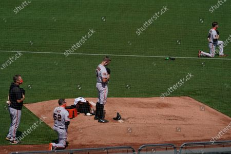 Stock Image of San Francisco Giants' Austin Slater, top right, and assistant Ethan Katz (52) kneel during the national anthem before a baseball game against the Oakland Athletics in Oakland, Calif., . Pictured at center is pitcher Tyler Anderson