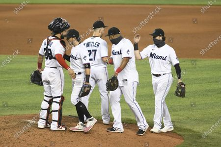 Miami Marlins celebrate after the team's baseball game against the Washington Nationals, in Miami. The Marlins won 2-1