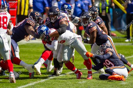 Stock Picture of Chicago, Illinois, U.S. - Bears #96 Akiem Hicks tackles Giants #26 Saquon Barkley during the NFL Game between the New York Giants and Chicago Bears at Soldier Field in Chicago, IL. Photographer: Mike Wulf