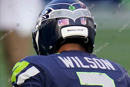 """Seattle Seahawks quarterback Russell Wilson wears the name """"Breonna Taylor"""" on his helmet during warmups before an NFL football game against the New England Patriots, in Seattle. NFL players have selected to wear the names of people this season who have been victims of police brutality in support of Black Lives Matter"""