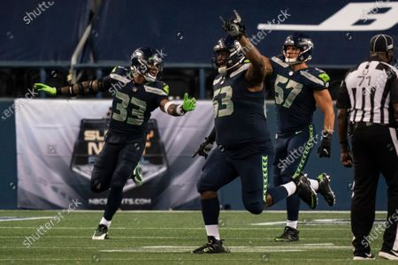 Seattle Seahawks', from left, Jamal Adams, Anthony Rush and Cody Barton celebrate after an NFL football game against the New England Patriots, in Seattle. The Seahawks won 35-30