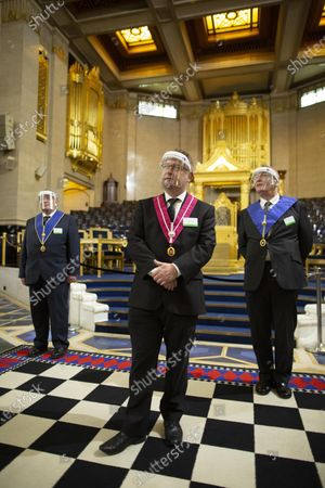 Stock Picture of Freemasons  (left) Martin Bullard, (centre) James Jarvis and (right) Ian Clark stood together in front of the throne inside the Grand Temple at the lodge in Covent Garden