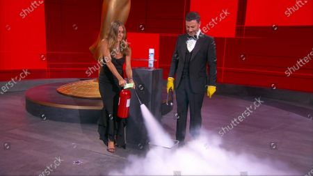 Jennifer Aniston, left, and Jimmy Kimmel sanitize the winner's envelope during the 72nd Emmy Awards telecast on at 8:00 PM EDT/5:00 PM PDT on ABC