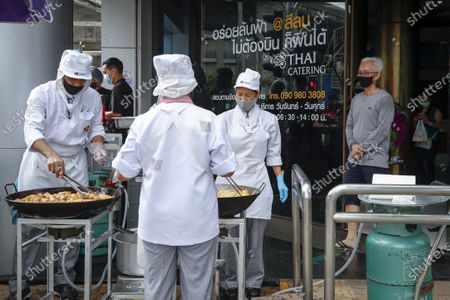 Thai Airways chefs prepare dough fritters, known as 'pa tong go', outside the new Thai Catering cafeteria at the Thai Airways office building in downtown Bangkok, Thailand, 21 September 2020. Thai Airways turned the company's downtown ticketing office into a cafeteria operated by Thai Catering. The cafeteria sells inflight-style meals and pastries, while customers queue up in long lines during morning hours to buy 'pa tong go', traditional dough fritters, mostly eaten for breakfast. Thai Catering staff as well as staff formerly employed in ticketing sales and customer service, now work at the cafeteria, helping keep the staff employed at a time when the company is experiencing major financial losses due to travel restrictions caused by the COVID-19 pandemic. On 14 September 2020, Thailand's Central Bankruptcy Court approved the airline's debt restructuring plan as the company was set to file for bankruptcy.