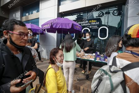 A woman buys pastries as other people queue up to buy dough fritters outside the Thai Airways office in downtown Bangkok, Thailand, 21 September 2020. Thai Airways turned the company's downtown ticketing office into a cafeteria operated by Thai Catering. The cafeteria sells inflight-style meals and pastries, while customers queue up in long lines during morning hours to buy 'pa tong go', traditional dough fritters, mostly eaten for breakfast. Thai Catering staff as well as staff formerly employed in ticketing sales and customer service, now work at the cafeteria, helping keep the staff employed at a time when the company is experiencing major financial losses due to travel restrictions caused by the COVID-19 pandemic. On 14 September 2020, Thailand's Central Bankruptcy Court approved the airline's debt restructuring plan as the company was set to file for bankruptcy.