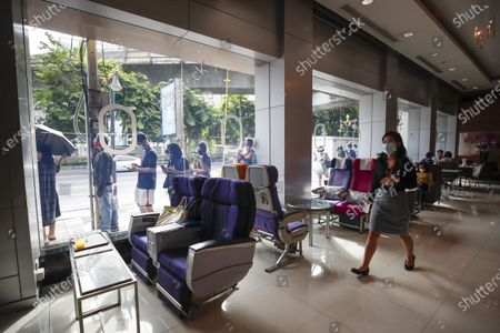 A Thai Airways staff member walks past airline seats as customers queue up outside the new Thai Catering cafeteria at the Thai Airways office building in downtown Bangkok, Thailand, 21 September 2020. Thai Airways turned the company's downtown ticketing office into a cafeteria operated by Thai Catering. The cafeteria sells inflight-style meals and pastries, while customers queue up in long lines during morning hours to buy 'pa tong go', traditional dough fritters, mostly eaten for breakfast. Thai Catering staff as well as staff formerly employed in ticketing sales and customer service, now work at the cafeteria, helping keep the staff employed at a time when the company is experiencing major financial losses due to travel restrictions caused by the COVID-19 pandemic. On 14 September 2020, Thailand's Central Bankruptcy Court approved the airline's debt restructuring plan as the company was set to file for bankruptcy.