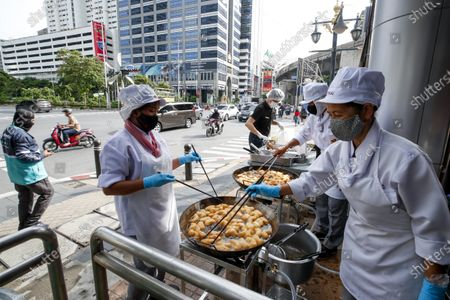 Stock Image of Thai Airways chefs prepare dough fritters, known as 'pa tong go', outside the new Thai Catering cafeteria at the Thai Airways office building in downtown Bangkok, Thailand, 21 September 2020. Thai Airways turned the company's downtown ticketing office into a cafeteria operated by Thai Catering. The cafeteria sells inflight-style meals and pastries, while customers queue up in long lines during morning hours to buy 'pa tong go', traditional dough fritters, mostly eaten for breakfast. Thai Catering staff as well as staff formerly employed in ticketing sales and customer service, now work at the cafeteria, helping keep the staff employed at a time when the company is experiencing major financial losses due to travel restrictions caused by the COVID-19 pandemic. On 14 September 2020, Thailand's Central Bankruptcy Court approved the airline's debt restructuring plan as the company was set to file for bankruptcy.
