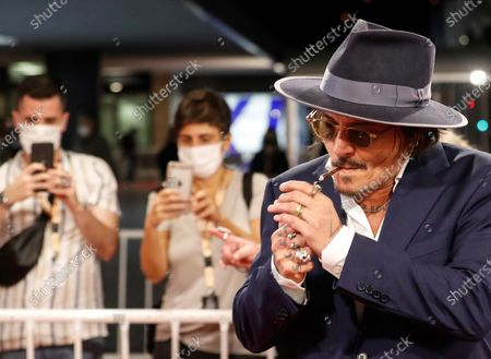 Johnny Depp (R) lights up a cigar upon arriving to the premiere of his film 'Crock of Gold: A few rounds with Shane MacGowan' as part of 68th San Sebastian International Film Festival in the city of San Sebastian, northern Spain, late 20 September 2020 (issued on 21 September 2020). The film competes in the official section of the festival running until 26 September.