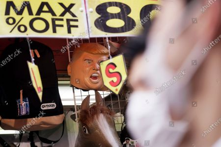Stock Picture of People wearing protective masks to help curb the spread of the coronavirus walk by a street stall selling rubber masks, including one depicting U.S. President Donald Trump, in Tokyo. The Japanese capital confirmed more than 90 coronavirus cases on Monday marking Respect-for-the-Aged Day holiday