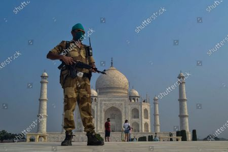 Paramilitary soldier wearing a mask stands guard as the Taj Mahal monument is reopened after being closed for more than six months due to the coronavirus pandemic in Agra, India, Monday, Sept.21, 2020